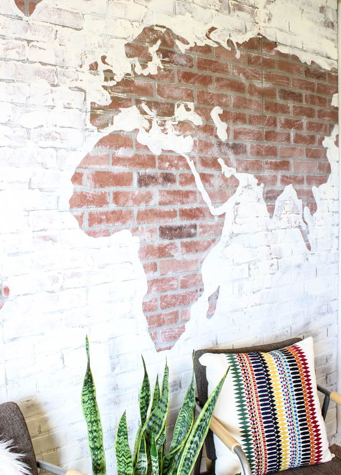 world map on brick accent wall with plant and chair