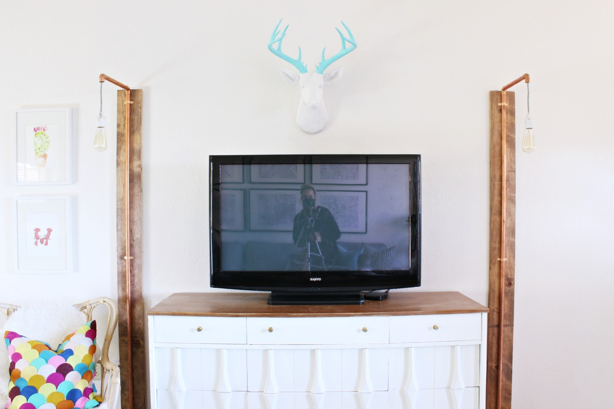 Sconces around TV stand and love the deer above! - Click for tutorial + details