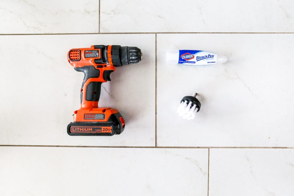 Using a bleach pen and power brush to clean grout